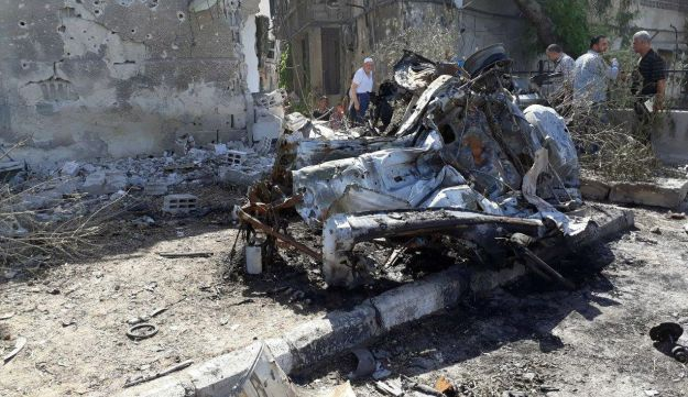 People inspect the site of a car bomb blast in Damascus in this handout picture posted on SANA on July 2, 2017, Syria.