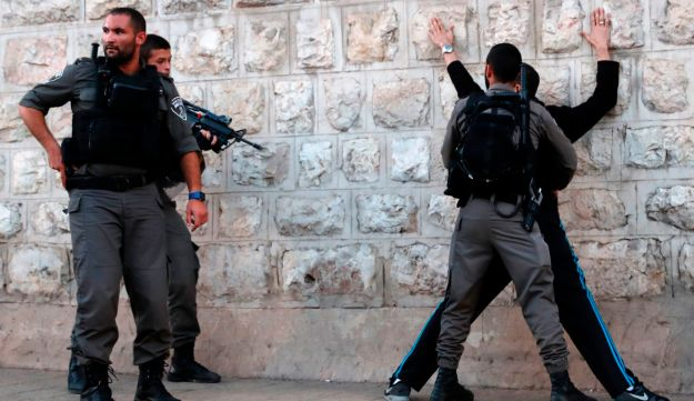 Israeli police search a Palestinian man outside Damascus Gate in Jerusalem's Old City on June 16, 2017, following the attack