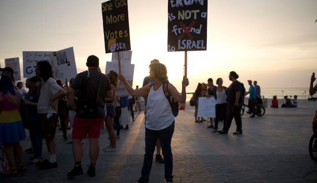 Israeli and American activists holds signs during a protest against President Donald Trump next to the U.S embassy in Tel Aviv. May 22, 2017