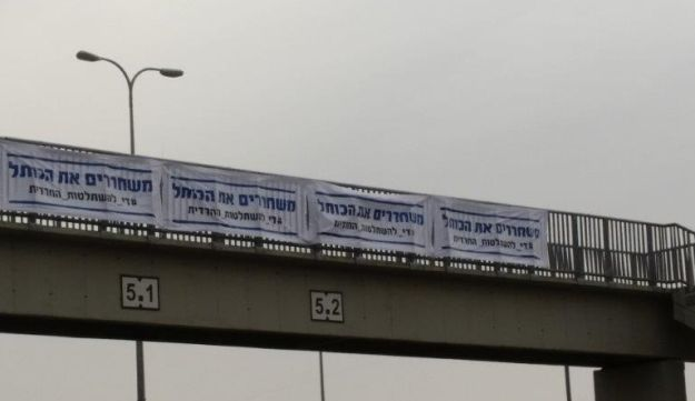 """Signs on a highway calling to: """"Free the Kotel – Enough with ultra-Orthodox domination."""""""