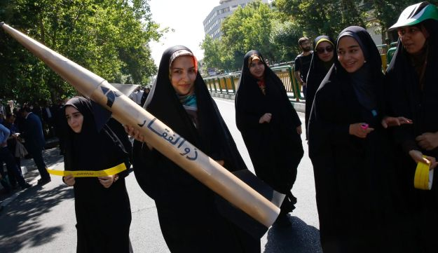 An Iranian girl holds a model of a missile during a rally marking al-Quds Day in Tehran, June 23, 2017.