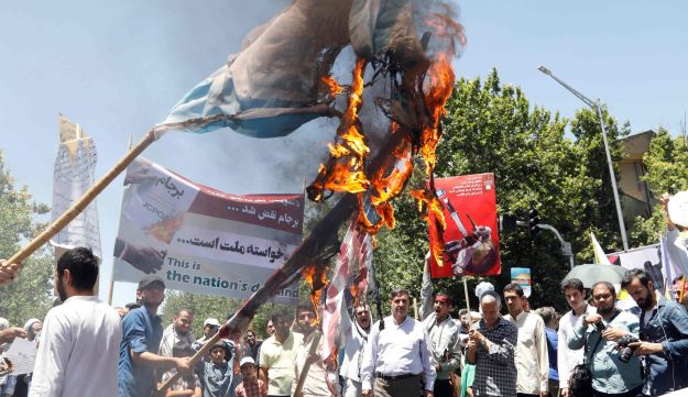 Iranians burn Israeli and American flags during a rally marking al-Quds day in Tehran, June 23, 2017.