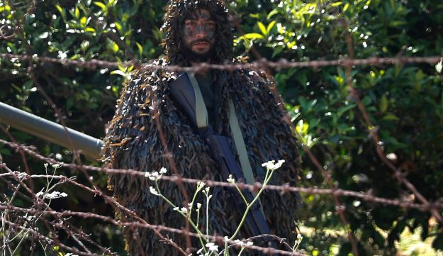 A Hezbollah fighter stands in orange trees in the coastal border town of Naqoura in south Lebanon, April 20, 2017.