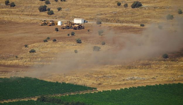 Smoke rises from a field on the Israeli side of the border with Syria after projectiles fired from the war-torn country hit the Israeli-occupied Golan Heights on June 24, 2017.