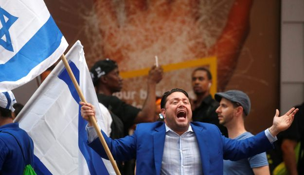 A pro-Israel demonstrator holds a flag and yells slogans across the street from a pen of Muslim anti Israel protesters during a demonstration in Times Square in the Manhattan borough of New York City, New York, U.S. June 23, 2017.