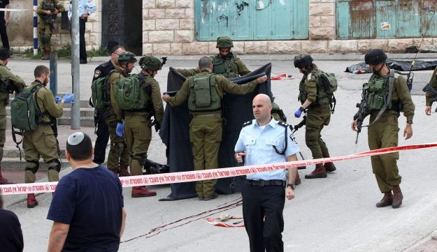 Israeli soldiers cover the body of a Palestinian assailant who was shot in head by an Israeli soldier as he lay wounded on the ground in Hebron, March 24, 2016.