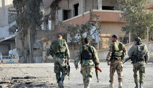 Syrian soldiers patrol the town of al-Quaryatayn in Syria's central Homs province, on April 3, 2016.