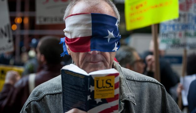 A protester wears a blindfold and holds a copy of the U.S. Constitution during a protest outside the New York State Republican Gala in New York, U.S., on Thursday, April 14, 2016.