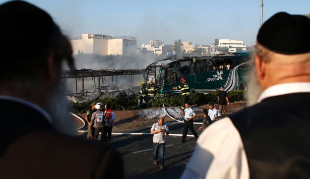 Jewish men look at the site of an explosion on bus in Jerusalem on April 18, 2016.