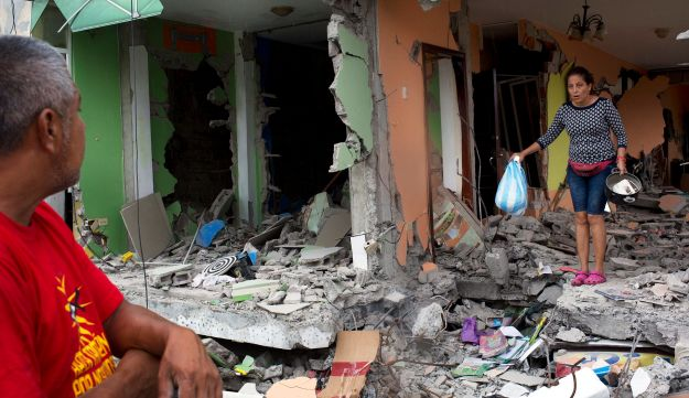 A woman leaves her brother's house after recovering usable items one week after the devastating earthquake, Pedernales, Ecuador, April 23, 2016.