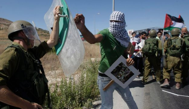 A Palestinian confronts an Israeli soldier during a demonstration near the West Bank town of Nablus, July 14, 2014.