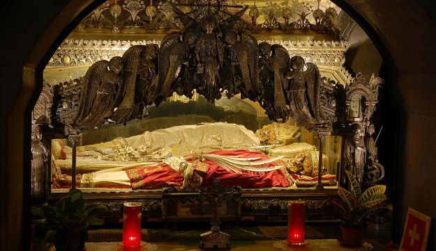 The body of the bishop of Milan, Ambrose, in white vestments, housed in the crypt of Sant'Ambrogio basilica. His remains lie (behind glass) with those of two martyrs, the saints Gervase and Protase.