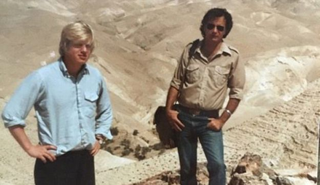 Britain's Foreign Secretary Boris Johnson on his first trip to Israel, in the summer of 1984. Johnson stands, arms akimbo, on rocks with desert mountains in the background and an unidentified man at his side.