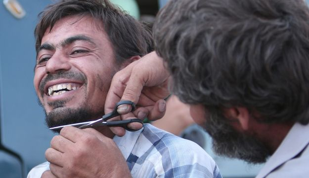 A man cuts the beard of a civilian who was evacuated with others by the Syria Democratic Forces from an ISIS-controlled neighborhood of Manbij, Syria, August 12, 2016.