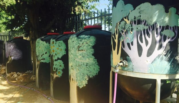 Yechieli system installed at  Hayovel elementary school, Jerusalem: Note the heightened, round-bottomed settling tank and series of storage tanks, prettily decorated with trees.