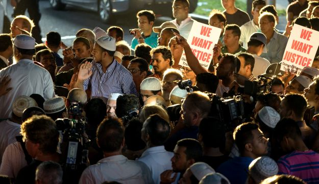 People gather for a demonstration Saturday, Aug. 13, 2016, near a crime scene after the leader of a New York City mosque and an associate were fatally shot as they left afternoon prayers.
