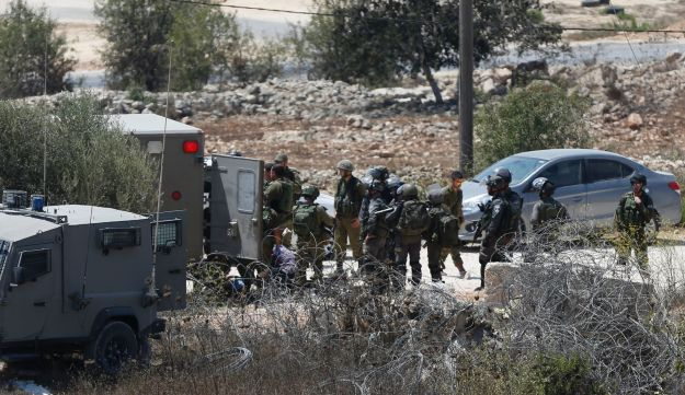 Israeli soldiers surround the body of a suspected Palestinian man who was reportedly shot dead by Israeli troops at the entrance to the West Bank village of Silwad on August 26, 2016.
