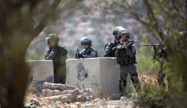 Israeli soldiers secure scene after Palestinian shot and killed by Israeli soldiers in the village of Silwad, near the West Bank city Ramallah, Friday, Aug. 26, 2015.