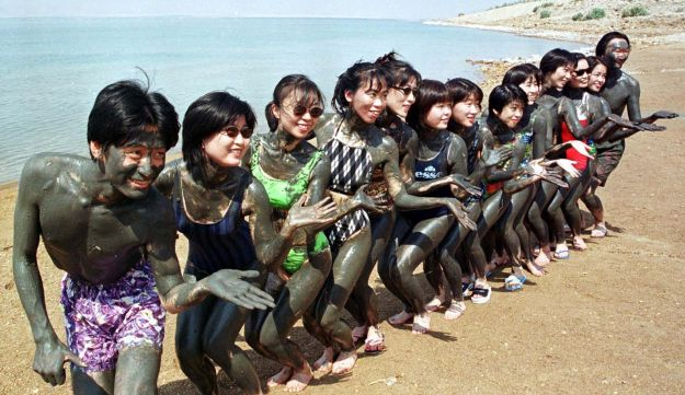 Japanese tourists covered by black mud at the Dead Sea.