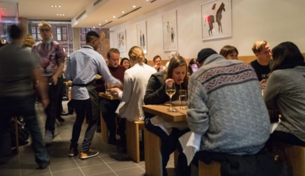Momofuku Nishi, in New York. People sit on backless benches in a spare, modern space.