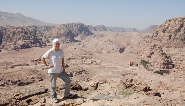 Leigh-Ann Bedal, wearing white head cover, white T-shirt and light-colored trousers, standing to side of view of desert and Petra city center, seen behind the right of her arm.