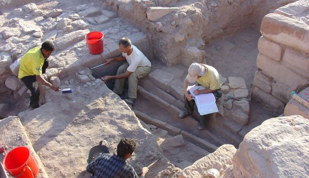 Excavating and documenting irrigation channels on the garden terrace. Photo shows four excavators, two red pails and well-preserved remains of walls and irrigation channels.