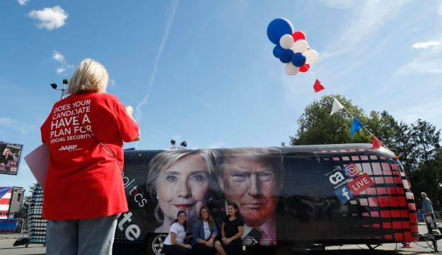 People pose for a photo kneeling near a bus adorned with photos of candidates Hillary Clinton and Donald Trump before the presidential debate at Hofstra University in Hempstead, N.Y., Monday, Sept. 26, 2016.