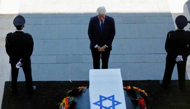 Former U.S. President Bill Clinton stands next to the coffin of former Israeli President Shimon Peres, as he lies in state at the Knesset plaza on September 29, 2016.