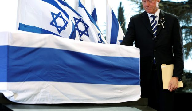 Former U.S. President Bill Clinton touches the coffin of former Israeli President Shimon Peres after delivering his eulogy at Peres's funeral in Jerusalem, 30 September 2016.