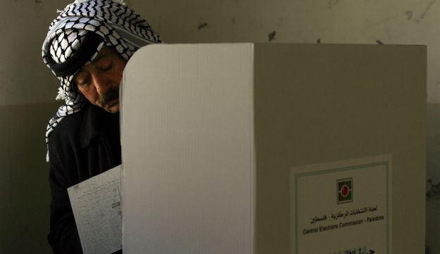 File photo: A Palestinian police officer fills in his ballot before casting it in parliamentary elections in the West Bank city of Nablus in 2006.