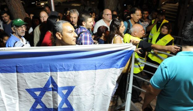 Israeli Arabs, and Jews, one of whom holds a national flag, head toward an Israeli Arab rapper's concert in Haifa on October 18, 2016.
