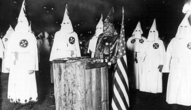 A Ku Klux Klan night rally in Chicago, around 1920. Picture shows several hooded persons in white robes with insignia, and one in black robes, near the altar, holding an American flag.