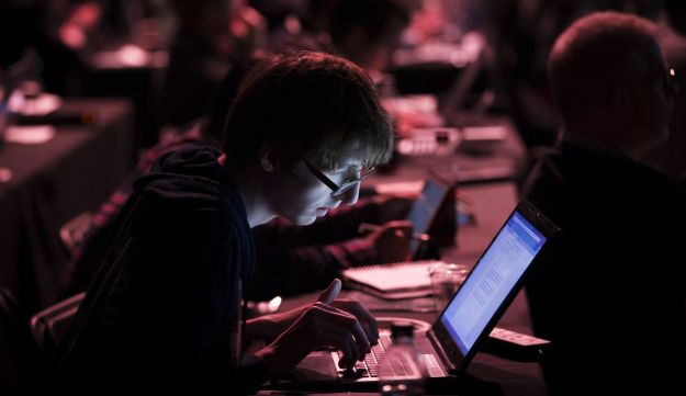 FILE PHOTO: An attendee works at his laptop during the TechCrunch Disrupt 2015 conference in London, U.K., on Monday, Dec. 7, 2015.
