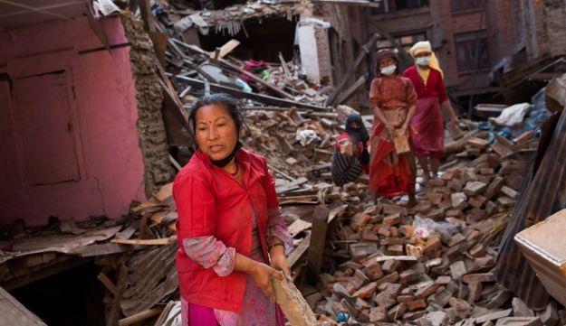 Nepalese women remove debris from their house that was destroyed during the earthquake in Bhaktapur, Nepal, Sunday, May 3, 2015.
