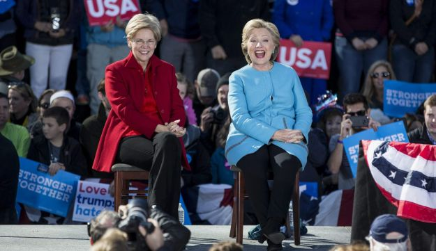 Senator Elizabeth Warren, a Democrat from Massachusetts (l), and Hillary Clinton, 2016 Democratic presidential nominee, smile while on stage during a campaign event in Manchester, New Hampshire, U.S., Oct. 24, 2016