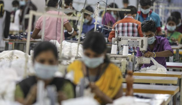 Employees use sewing machines on a production line at a clothing factory in Tiruppur, Tamil Nadu, India, Aug. 4, 2016.