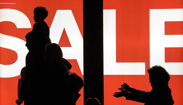 The silhouettes of pedestrians are seen in front of a 'Sale' sign displayed in the window of an H&M store in downtown San Francisco, California, U.S., Dec. 28, 2015.