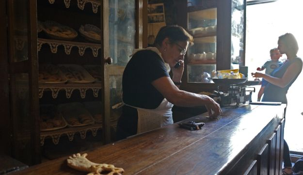 Herminia Rodriguez, left, preparing change for a customer at her Jewish bakery in Ribadavia, Sept, 24, 2016.