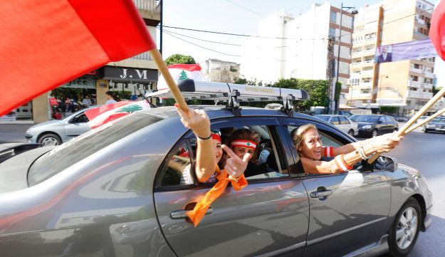 Supporters of Lebanese president Michel Aoun waving political flags in the outskirts of Beirut, October 31, 2016.
