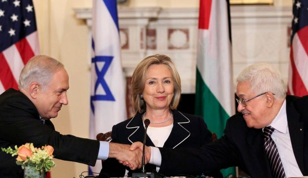 Then-Secretary of State Hillary Clinton looks on as PM Benjamin Netanyahu and PA President Mahmoud Abbas shake hands in 2010.