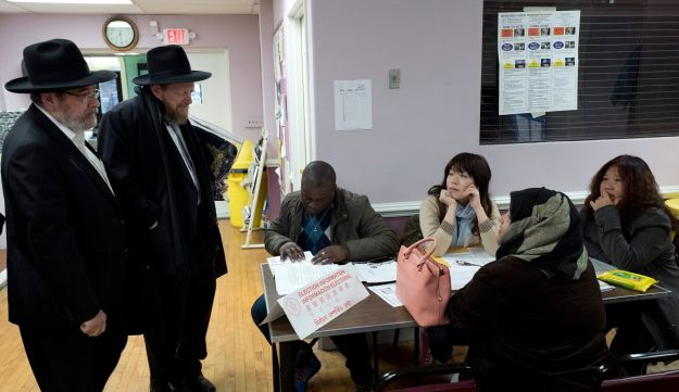 Jewish voters, left, confirming their addresses with poll worker before voting, Tuesday, Nov. 8, 2016, in the Boro Park neighborhood in the Brooklyn borough of New York.