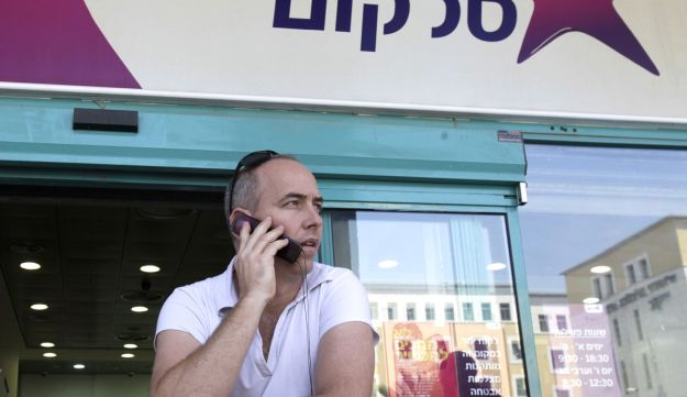 A customer uses a mobile handset outside a Cellcom Israel Ltd. store in the Ramat Gan district of Tel Aviv, Israel, August 18, 2011.