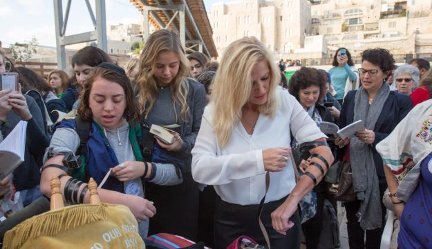 Women put on tefillin at the Western Wall in Jerusalem, November 2, 2016.
