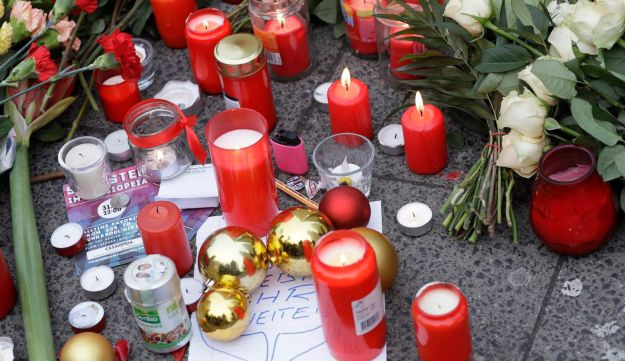 Candles burn near the crime scene in Berlin, Germany, December 20, 2016, the day after a truck ran into a crowded Christmas market and killed several people.