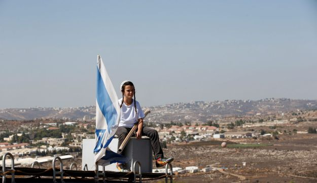 A boy sits near an Israeli flag atop the roof of a vehicle at the entrance to the Jewish settler outpost of Amona in the West Bank October 20, 2016.