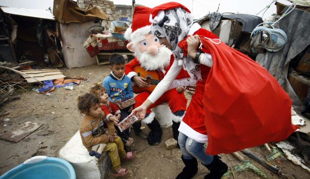 An Iraqi odontology student dressed in a Santa Claus outfit distribute gifts to impoverished children outside their shanty home in the Iraqi holy Shiite city of Najaf on December 25, 2016