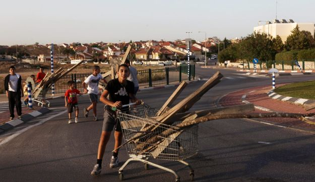 Kids use a shopping cart to transport firewood for a Lag Ba'Omer bonfire, Netivot, March 4, 2013.