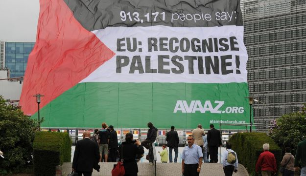 "A Palestinian flag, bearing the slogan: ""EU recognize Palestine"" sponsored by the non-governmental U.S. organization Avaaz.org, flies in front of European Union headquarters in Brussels. September 12, 2011"