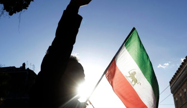A demonstrator waves the flag of the former Imperial State of Iran outside the Iranian Embassy in Rome, Tuesday, Jan. 2, 2018.