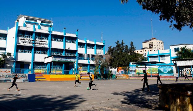 Palestinian refugee boys play football inside the UNRWA school in Gaza City on January 8, 2018.